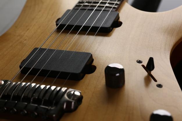 Hölzerne e-gitarre der klassischen form mit rosenholzhalsnahaufnahme. sechs aufgereihtes hölzernes gitarrenkonzept des weinlesestadiums der musikerschulbildungskunstfreizeit elektrischen