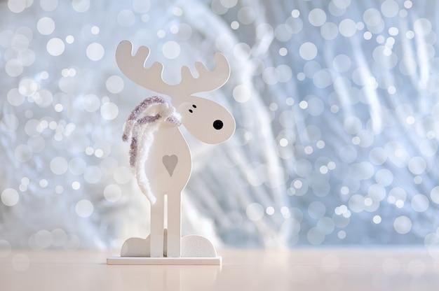 Hölzerne elche der weißen weihnacht mit einem herzen auf blau