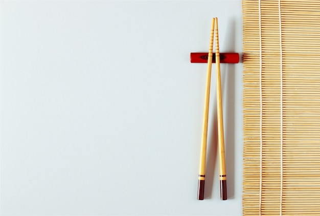 Hölzerne essstäbchen auf weißer tabelle mit bambusmatte, kopienraum.