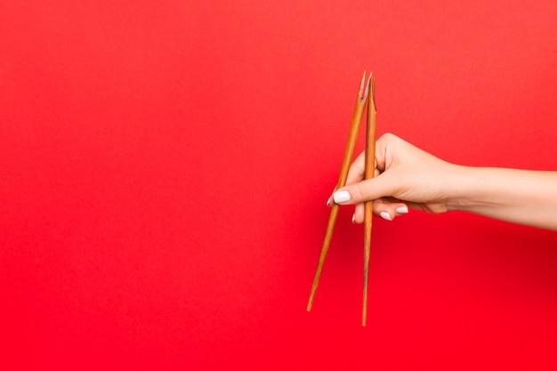 Hölzerne essstäbchen gehalten mit den weiblichen händen auf rotem hintergrund. essfertiges s mit leerem raum