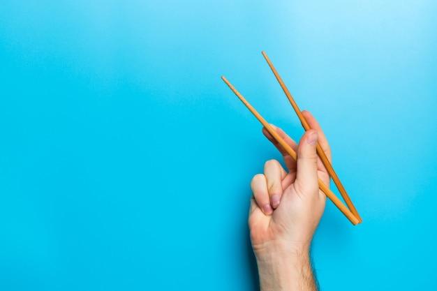 Hölzerne essstäbchen in der männlichen hand auf schwarzem mit emptyfor ihre idee. leckeres essen
