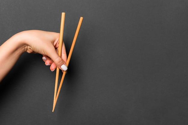 Hölzerne essstäbchen mit weiblichen händen auf schwarzem hintergrund gehalten. bereit für essenskonzepte mit leerem raum.