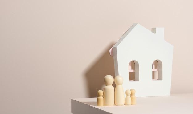 Hölzerne familienfiguren, modellhaus auf beigem hintergrund. immobilienkauf, mietkonzept. umzug in neue wohnungen