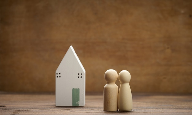 Hölzerne familienfiguren, modellhaus auf braunem hintergrund. immobilienkauf, mietkonzept. umzug in neue wohnungen