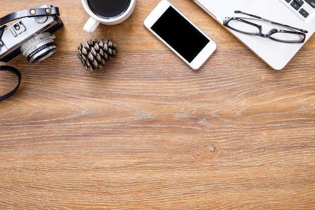 Hölzerne fotografschreibtischtabelle mit filmkamera, smartphone, laptop-computer, tasse kaffee und versorgungen.
