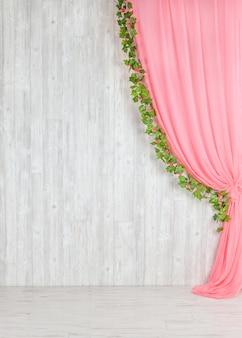 Hölzerne graue wand mit einem rosa vorhang und blumen.