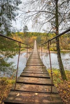 Hölzerne hängebrücke über dem fluss im wald