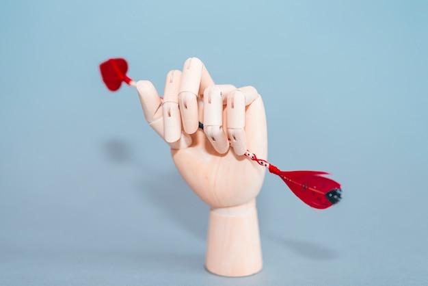 Hölzerne hand, die liebespfeil hält
