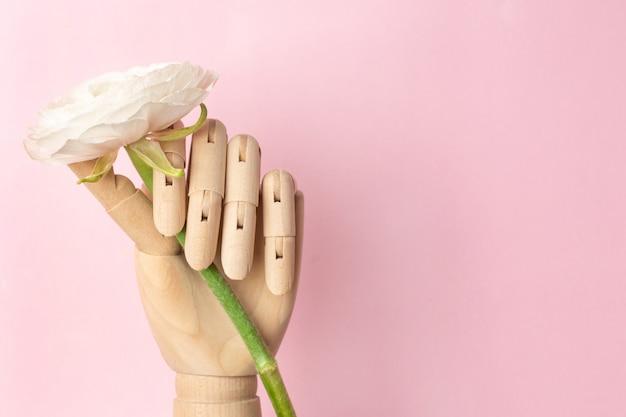 Hölzerne hand mit einer weißen blume auf einem rosa