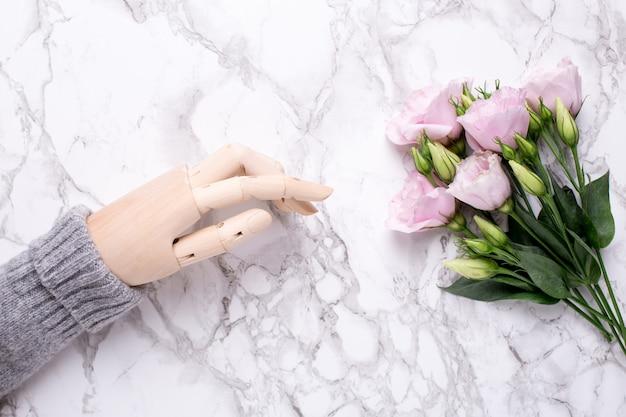 Hölzerne hand mit rosa blumen auf marmor