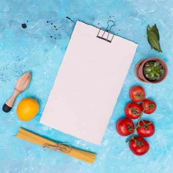 Hölzerne handpresse; zitrone; ungekochte spaghetti-nudeln; rote tomaten; grüne lorbeerblätter und kaktuspflanze mit weißem leerem papier auf blauem grunge hintergrund