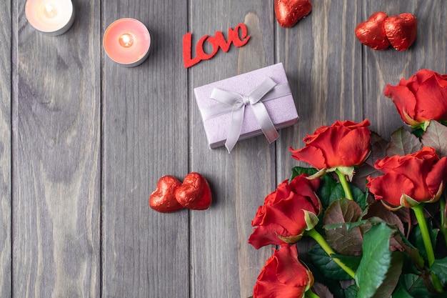 Hölzerne hintergrundkarte des romantischen heilig-valentinsgrußes mit blumenstrauß von schönen roten rosen und von geschenk