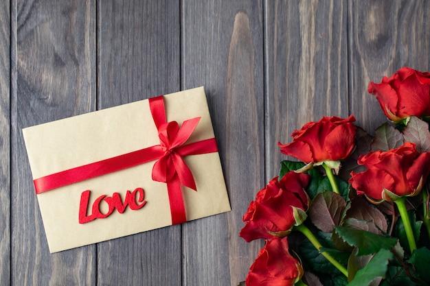 Hölzerne hintergrundkarte des romantischen heilig-valentinsgrußes mit blumenstrauß von schönen roten rosen und von liebesgeschenkumschlag