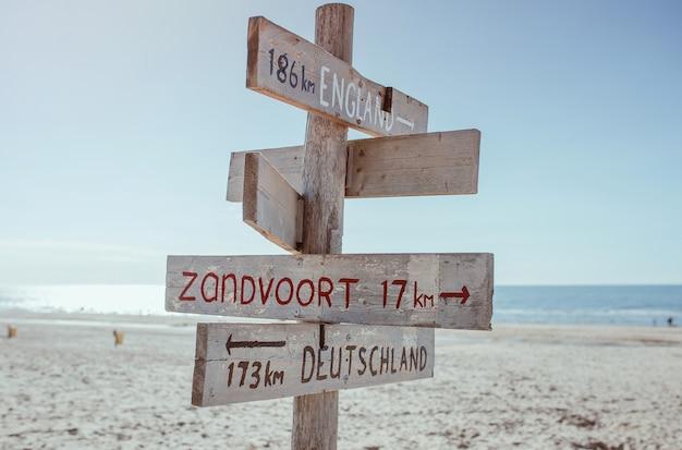 Hölzerne informationstafel mit entfernung nach england deutschland und zandvoort am strand nordsee north