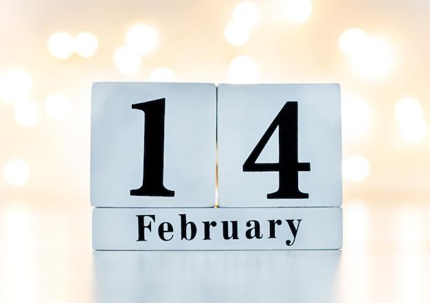 Hölzerne kalendershow vom 14. februar mit goldenem bokeh auf der rückseite. konzept valentinstag.