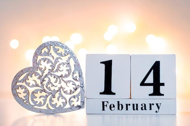 Hölzerne kalendershow vom 14. februar mit holzherz und goldenem und rotem bokeh auf der rückseite. konzept valentinstag.