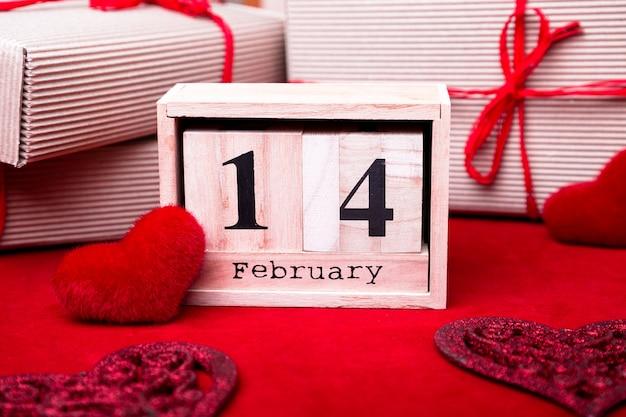 Hölzerne kalendershow vom 14. februar mit rotem herzen und geschenkboxen.