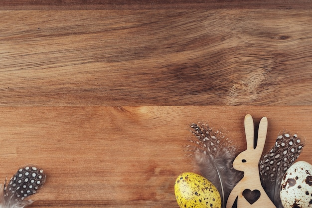 Hölzerne kaninchen und ostereier, flache lage, draufsicht, kopienraum. ostern-konzept. festliche osterdekoration auf einem hölzernen hintergrund. heller hintergrund im retro-stil. grußkarte.