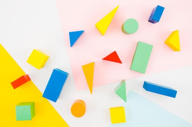 Hölzerne kinderspielwaren der draufsicht mit buntem hintergrund