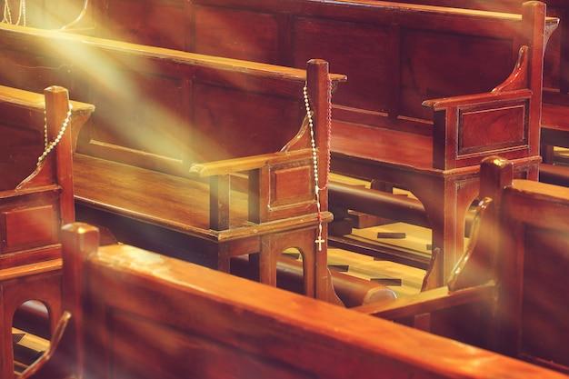 Hölzerne kirchenbänke in den kirchen- und rosenkranzperlen mit sonnenlicht