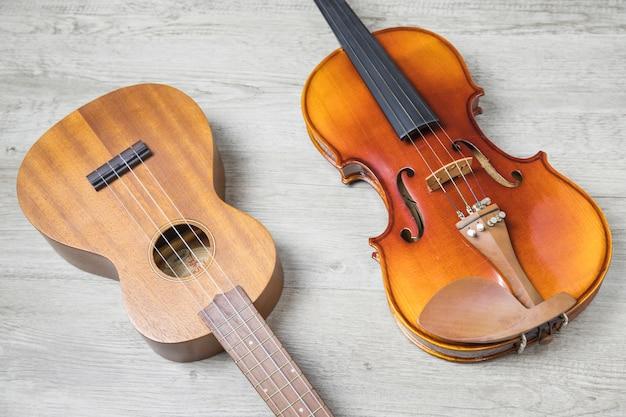 Hölzerne klassische gitarre und violine auf strukturiertem hintergrund