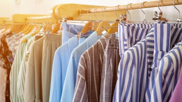 Hölzerne kleiderbügel mit modischer bunter sommerkleidung auf einem regal im modernen designerladen in der nähe des sonnenlichts