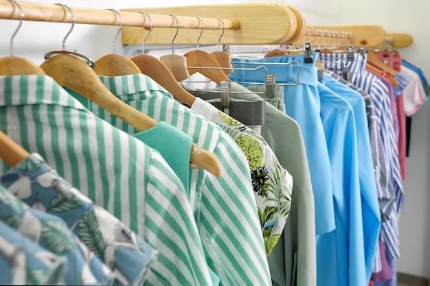 Hölzerne kleiderbügel mit modischer bunter sommerkleidung auf einem regal in einer modernen designer-shop-nahaufnahme