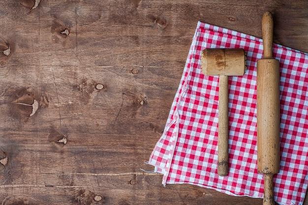Hölzerne küchenartikel auf einer roten serviette, einem nudelholz und einem hammer für das schlagen des fleisches