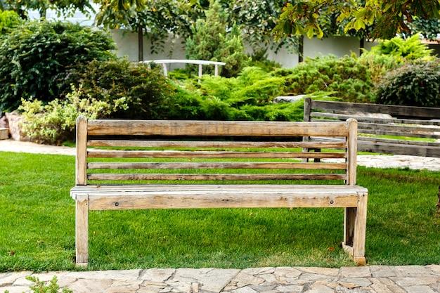 Hölzerne leere bank in einem stadtpark. guter ort zum entspannen an einem sommertag.