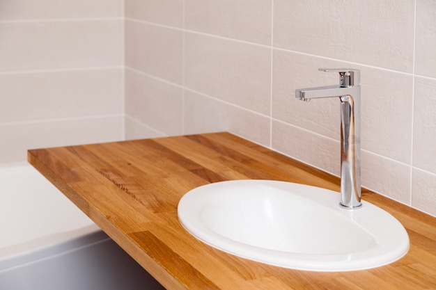 Hölzerne leere tischplatte des braunen teakholzes der nahaufnahme mit weißer runder keramischer wanne und hohem silbernem wasserhahn. reparatur, badrenovierung in wohnungen, hotel, spa