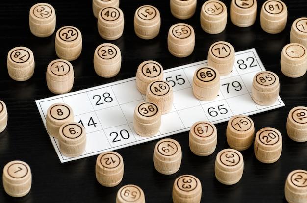 Hölzerne lottofässer und -karte für das spielen auf einer schwarzen tabelle