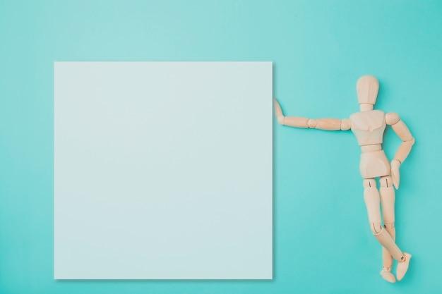 Hölzerne marionette zeigt beiseite mit seiner hand- und papierkartenanmerkung