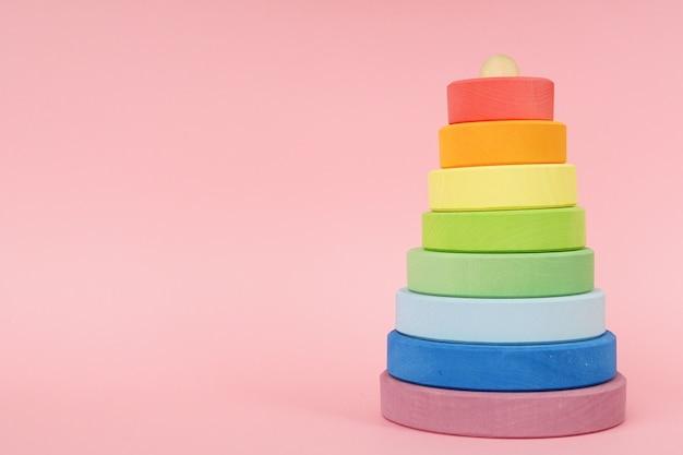Hölzerne mehrfarbige pyramide der kinder auf einem rosa hintergrund mit copyspace