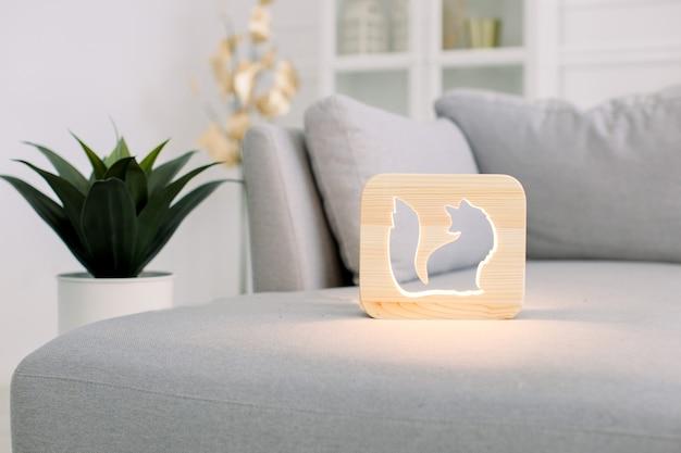 Hölzerne nachtlampe mit ausgeschnittenem fuchsbild, auf grauem monochromem sofa, im stilvollen hellen innenraum des wohnzimmers