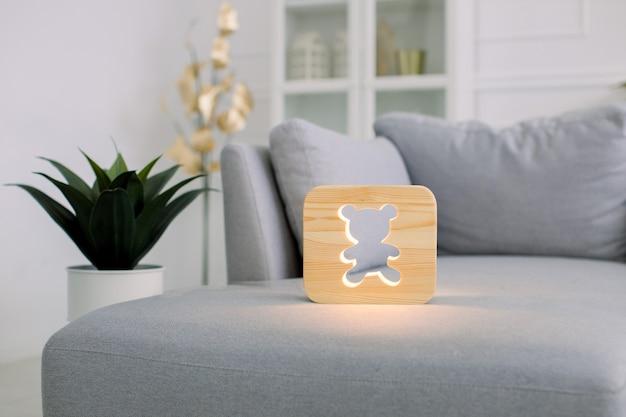 Hölzerne nachtlampe mit bärenbild, auf grauem sofa, im stilvollen hellen hauptwohnzimmerinnenraum mit grünem blumentopf