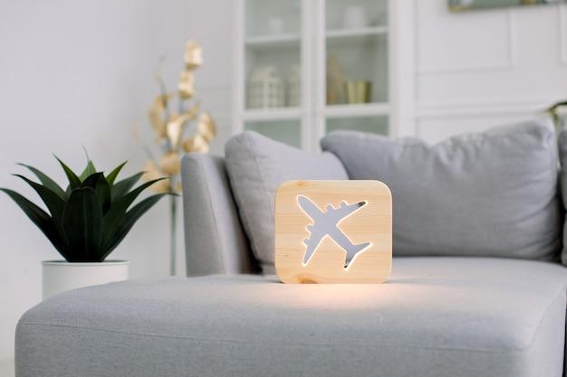 Hölzerne nachtlampe mit flugzeugbild, auf grauem monochromem sofa, im stilvollen hellen hauptwohnzimmerinnenraum