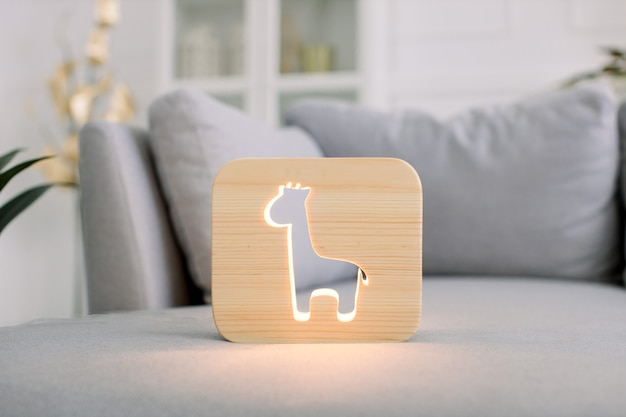 Hölzerne nachtlampe mit giraffenbild, auf grauem weichem bequemem sofa, im stilvollen hellen hauptwohnzimmerinnenraum.