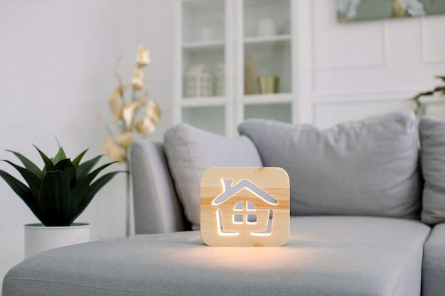 Hölzerne nachtlampe mit hausbild, auf grauem monochromem sofa, im stilvollen hellen hauptwohnzimmerinnenraum