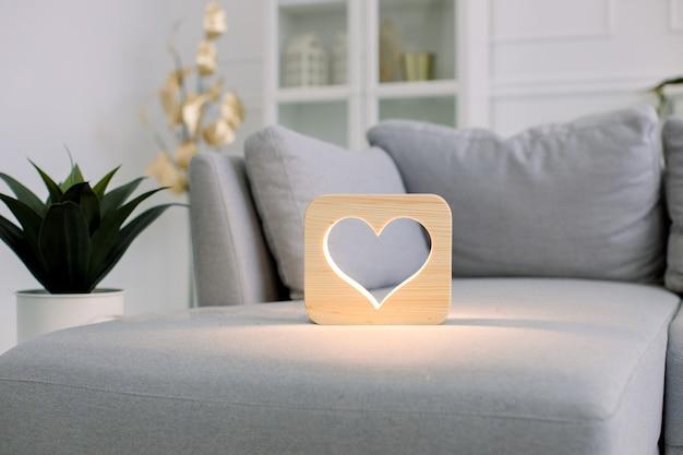 Hölzerne nachtlampe mit herzbild, auf grauem monochromem sofa, im stilvollen hellen hauptwohnzimmerinnenraum