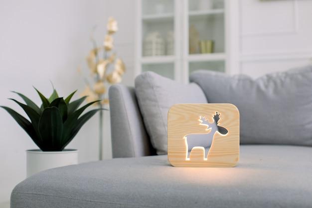 Hölzerne nachtlampe mit hirschbild, auf grauem kuscheligem weichem sofa, im stilvollen hellen hauptwohnzimmerinnenraum.