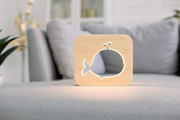 Hölzerne nachtlampe mit walbild, auf grauem monochromem sofa, im stilvollen hellen hauptwohnzimmerinnenraum.