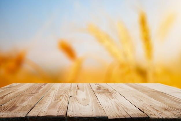 Hölzerne oberfläche auf unscharfem hintergrund des blauen himmels des weizens closeup