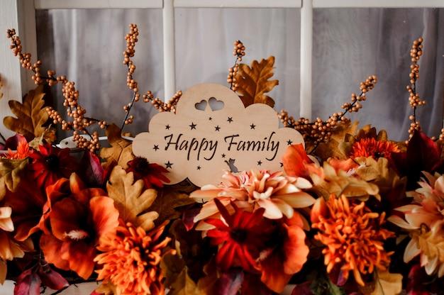 Hölzerne plakette mit der glücklichen familie der aufschrift unter blumen