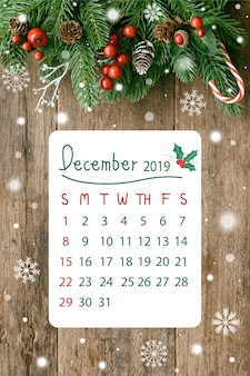 Hölzerne planke in der vertikale mit kiefernblättern und kegeln, stechpalmenbälle, schnee und zuckerstange im weihnachtskonzept mit kalender im dezember 2019