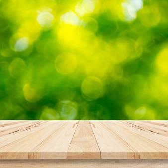 Hölzerne planke mit abstraktem natürlichem grün verwischte bokeh hintergrund für produktanzeige