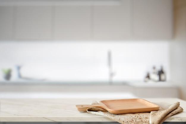 Hölzerne platte auf weißer tabelle im küchenraumhintergrund und kopienraum für produkt- oder lebensmittelmontage