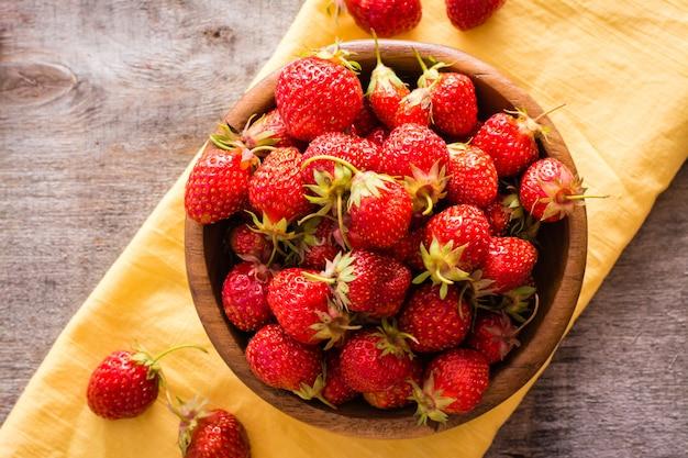 Hölzerne platte mit erdbeeren auf einer serviette auf dem tisch. ansicht von oben