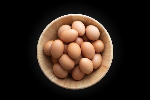 Hölzerne platte mit rohen eiern auf lokalisiertem hintergrund, draufsicht.