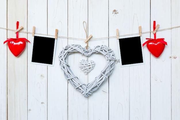 Hölzerne rustikale dekorative herzen und fotorahmen hängen auf vintage holz hintergrund mit platz.