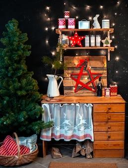 Hölzerne rustikale innenküche auf schwarzem hintergrund und rotem weihnachtsdekor.
